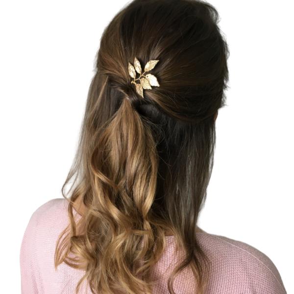 Frau mit lockigem Haar und goldenem Haarschmuck in Form von Blättern