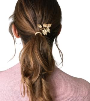 Frau mit gewelltem Zopf, in dem goldener Haarschmuck in Form von Blättern steckt.
