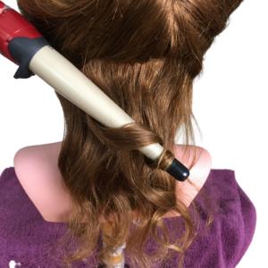 Haare werden mit einem Lockenstab gelockt.